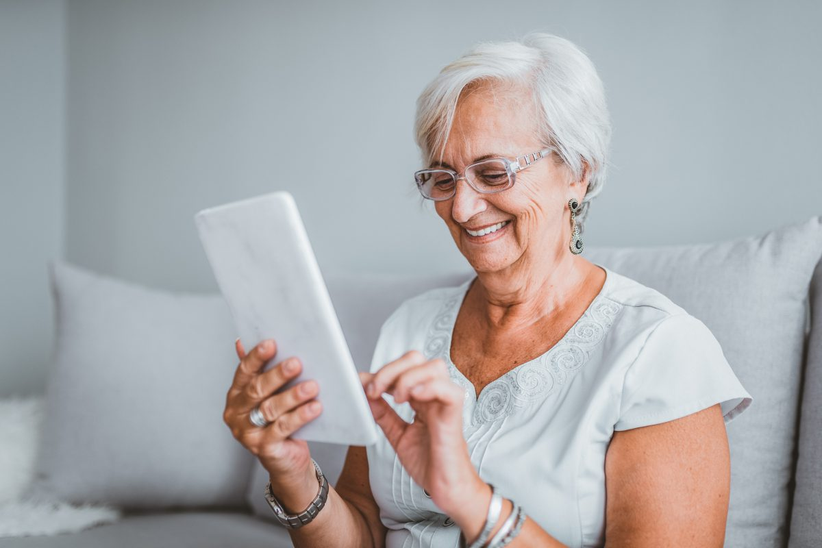 Portrait of senior woman using electronic tablet at home. Middle-aged woman reading a message, e-book or information on her tablet computer with a look of excited anticipation as she sits on a couch at home